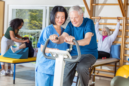 Elderly man on exercise bike being guided by a rehabilitation specialist.
